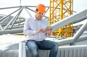stock photo of supervision  - A foreman with digital tablet at the construction supervising the project - JPG