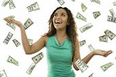 picture of save money  - Stock image of woman standing with open arms amidst falling money - JPG