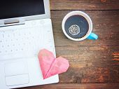 image of web surfing  - Laptop or notebook with cup of coffee and origami heart on old wooden table  - JPG