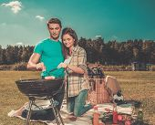 picture of grilled sausage  - Young couple preparing sausages on a grill outdoors  - JPG