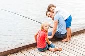 pic of fishing rod  - Happy father fishing with his kids while sitting at the riverbank together - JPG