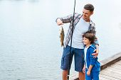 stock photo of rod  - Father holding fishing rod and showing big fish to his son - JPG