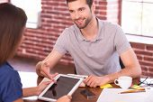 stock photo of casual wear  - Two cheerful people in casual wear sitting face to face at the table while man pointing digital tablet and smiling  - JPG