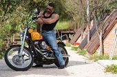 stock photo of biker  - Biker Man Bodybuilder Sits On A Bike - JPG