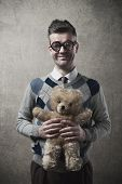pic of teddy  - Childish funny guy with glasses holding a cute teddy bear - JPG