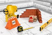 picture of mixer  - building blueprints with a cement mixer bags of cement a brick wall and other building tools concept of construction site  - JPG
