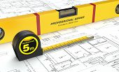pic of spirit  - close up view of spirit level and a tape measure on a building blueprint  - JPG