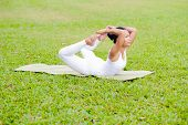 image of dhanurasana  - Beautiful woman practicing yoga in the park - JPG
