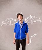 stock photo of nasty  - Young nasty man with devil horns and wings drawing - JPG