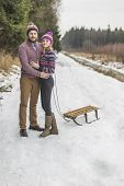 foto of sled  - Happy couple pulling sled in winter snowy wood - JPG