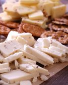 image of cut  - Crackers and cheese cut up and displayed on a cutting board - JPG