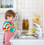 image of child development  - Lovely blond kid boy washing dishes in domestic kitchen - JPG