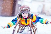 stock photo of cute  - Cute little funny boy in colorful winter clothes having fun on snow sledge outdoors during snowfall - JPG