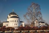 stock photo of brest  - White Orthodox Church among the remains of the ramparts of the Brest Fortress in Belarus under a winter tree - JPG