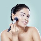 pic of face-powder  - Pretty young woman using makeup powder on her face by brush shot in studio against blue background - JPG