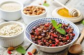 stock photo of quinoa  - oatmeal nuts quinoa granola on a dark wood background - JPG