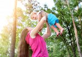 stock photo of rapture  - Young Mother and Happy Child in the Summer Park - JPG