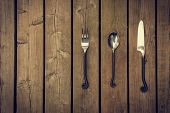foto of rapier  - Antique style cutlery a fork spoon and knife with twirled rapier like work metal stems against a natural wooden board background - JPG