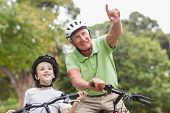 pic of grandfather  - Happy grandfather with his granddaughter on their bike on a sunny day - JPG