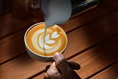 pic of latte  - Making of cafe latte art on the wooden table - JPG