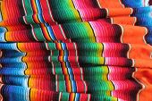 stock photo of mexican fiesta  - mexican handwoven rug poncho fiesta with stripes and bright colors  - JPG