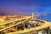 stock photo of shipyard  - Container Cargo freight ship with working crane bridge in shipyard under Stonecutters highway bridge at sunset for Logistic Import Export - JPG