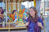 foto of carousel horse  - Happy beautifull girl stands in front of a carousel in a amusement park - JPG