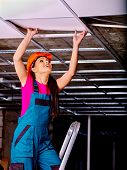stock photo of suspenders  - Woman in builder hardhat and uniform installing suspended ceiling - JPG