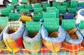 foto of stall  - Several bags containing typical spices for cooking with tags reporting names and prices are exposed on a market stall along the road in Sainte Anne Guadeloupe - JPG