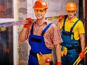 stock photo of millwright  - Two handsome men in builder uniform indoor - JPG