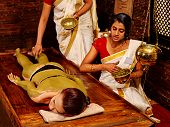 stock photo of ayurveda  - Young woman having green clay body Ayurveda spa massage - JPG