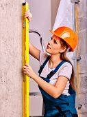 stock photo of millwright  - Happy woman with level in builder uniform indoor - JPG