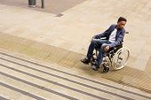 picture of staircases  - young man in a wheelchair at the bottom of a staircase unable to continue - JPG