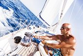 stock photo of rope pulling  - Handsome man working on sailboat - JPG