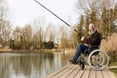 foto of wheelchair  - a young man in a wheelchair fishing - JPG