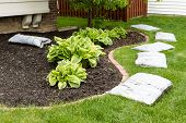 foto of manicured lawn  - Preparing to mulch the garden in spring laying out a row of commercial organic mulch in bags around the edge of the flowerbed on a neatly manicured green lawn - JPG