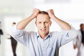 stock photo of pulling hair  - Frustrated mature man pulling his hair - JPG