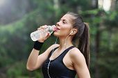 Постер, плакат: Healthy Lifestyle Sporty Woman With Headphone Drinking Water In Beautiful Nature Area