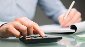 stock photo of calculator  - A female accountant uses a calculator and takes notes on a paper notebook on an office desk. ** Note: Shallow depth of field - JPG