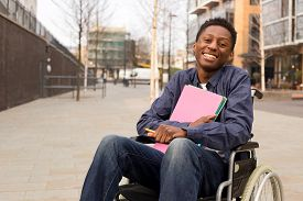 stock photo of wheelchair  - happy young disabled man in a wheelchair holding folders - JPG