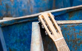 stock photo of dumpster  - Old unwanted guitar thrown away in an rusty metal dumpster - JPG