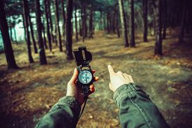 stock photo of pov  - POV image of traveler woman holding a compass and pointing direction in the forest - JPG