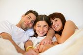 stock photo of matinee  - Portrait of a smiling family in a bed - JPG