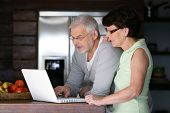 stock photo of 55-60 years old  - Portrait of a senior couple with a laptop computer - JPG