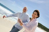 stock photo of 55-60 years old  - Portrait of a senior couple walking on the beach - JPG