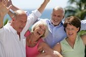 stock photo of 55-60 years old  - Portrait of senior couples smiling with arms up - JPG
