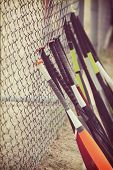 Постер, плакат: Youth baseball bats lined up against a chain link fence in batting cage