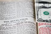 picture of revelation  - The dollar as a book mark in the background in an old King James Bible opened to the last book - JPG