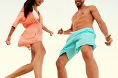 Couple dancing together at beach party. Two young people wearing beachwear and shorts having fun on  poster