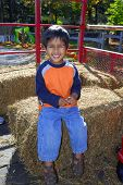 stock photo of hayride  - An handsome indian kid having fun with hay ride - JPG